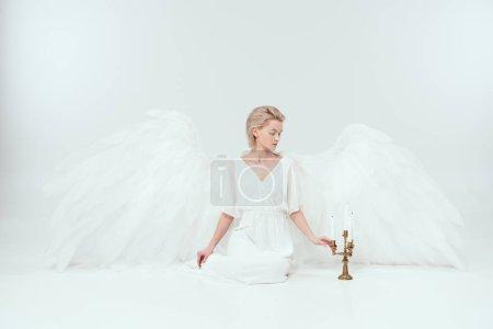 Foto de Hermosa mujer en traje de Ángel con alas, sentado cerca de candelabro con velas aislados en blanco - Imagen libre de derechos