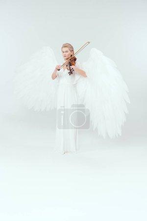Photo pour Belle femme en costume d'ange avec des ailes regardant la caméra et jouant du violon isolé sur blanc - image libre de droit