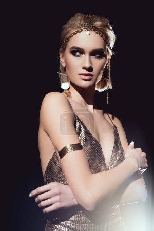 Photo pour Belle femme en accessoires dorés avec bras croisés posant sur fond noir - image libre de droit
