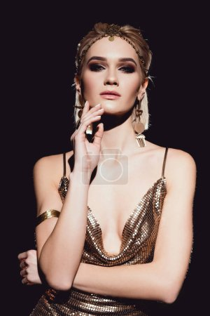 Photo pour Belle femme en accessoires dorés posant et regardant la caméra isolée sur noir - image libre de droit