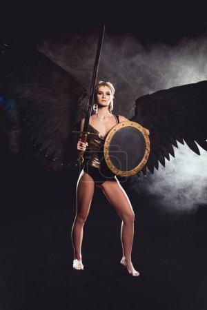 schöne Frau im Kriegerkostüm und Engelsflügeln, die in die Kamera schaut, während sie mit Schild und Schwert auf schwarzem Hintergrund posiert