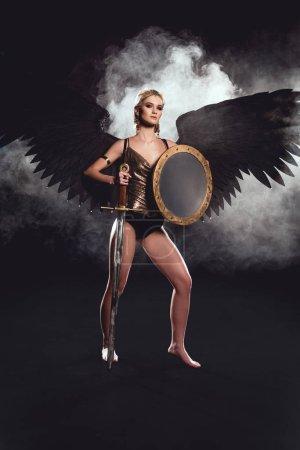 Photo pour Belle femme en costume de guerrier et ailes d'ange posant avec bouclier et épée sur fond noir - image libre de droit