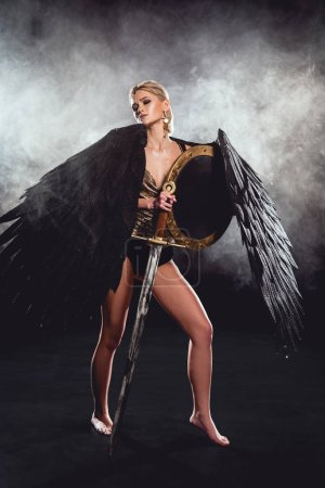 Photo for Beautiful woman in warrior costume and angel wings posing with shield and sword on black background - Royalty Free Image