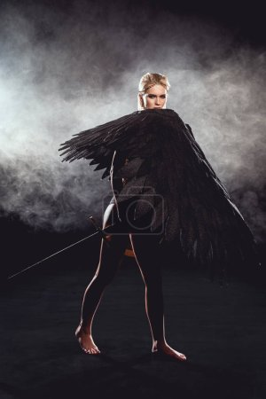 Foto de Hermosa mujer con alas de Ángel con espada y posando sobre fondo negro - Imagen libre de derechos