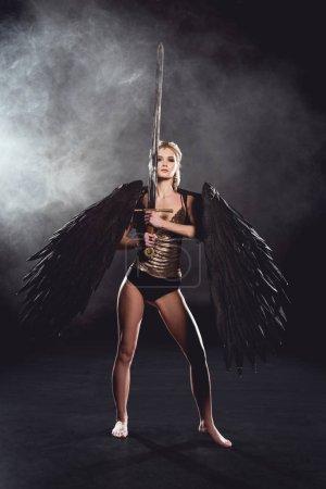 Photo pour Belle femme en costume de guerrier avec des ailes d'ange tenant épée, regardant la caméra et posant sur fond noir de fumée - image libre de droit