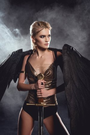 Photo for Beautiful woman in warrior costume with black angel wings holding sword and posing on dark smoky background - Royalty Free Image