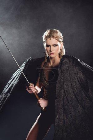 schöne aggressive Frau im Kriegerkostüm mit Engelsflügeln, Schwert in der Hand und Blick in die Kamera auf schwarzem Hintergrund
