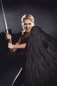 """Постер, картина, фотообои """"красивая сердитый женщина в костюме воин с крыльями ангела мечом и позирует на черном фоне"""""""