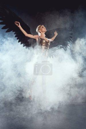 Photo pour Belle femme sexy avec des ailes d'ange noir sauter sur fond fumé - image libre de droit