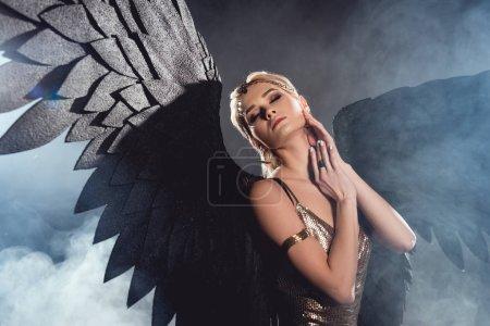 schöne sexy Frau mit schwarzen Engelsflügeln und goldenen Accessoires, die Gesicht berühren und auf dunklem rauchigen Hintergrund posieren