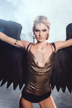schöne sexy Frau mit schwarzen Engelsflügeln und ausgestreckten Händen, die in die Kamera schauen, während sie auf dunklem Hintergrund posiert