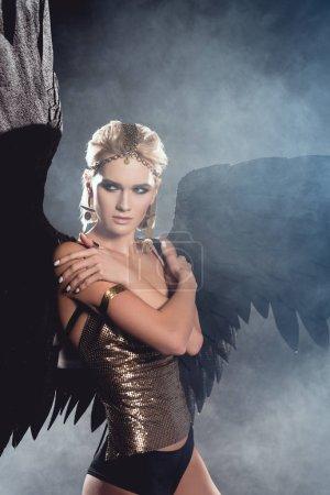 schöne junge sexy Frau mit schwarzen Engelsflügeln und goldenen Accessoires posiert auf dunklem rauchigen Hintergrund