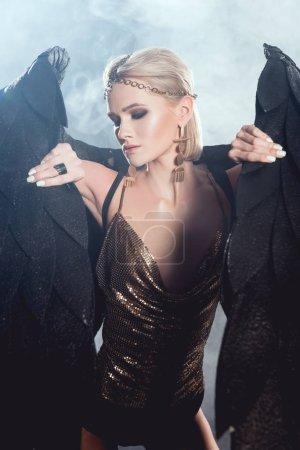 Foto de Hermosa mujer sexy en accesorios dorados sosteniendo alas de Ángel negro y posando sobre fondo oscuro - Imagen libre de derechos