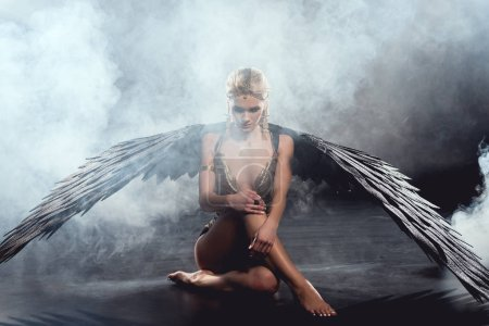 Photo for Beautiful sexy woman with black angel wings sitting and posing on dark background - Royalty Free Image