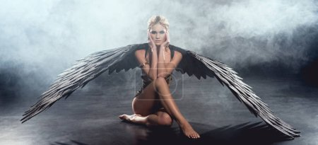 Photo for Beautiful sexy woman with black angel wings sitting, touching face and posing on dark background - Royalty Free Image