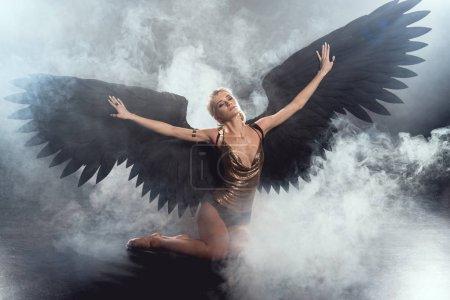 Photo pour Belle femme sexy avec des ailes d'ange noir et mains tendues assis et posant sur fond fumé foncé - image libre de droit