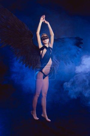 Foto de Hermosa mujer sexy con encaje máscara y alas de Ángel negro de pie de puntillas y posando sobre fondo azul oscuro - Imagen libre de derechos