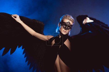 schöne sexy Frau mit Spitzenmaske und schwarzen Engelsflügeln schaut in die Kamera, während sie auf dunkelblauem Hintergrund posiert