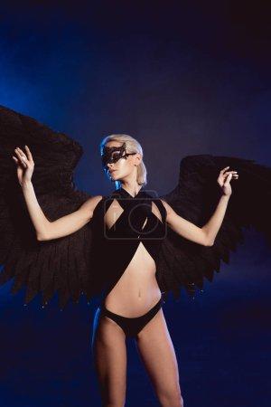 Photo pour Belle sexy femme mystérieuse dans le masque de la dentelle et des ailes d'ange noir posant sur fond sombre - image libre de droit