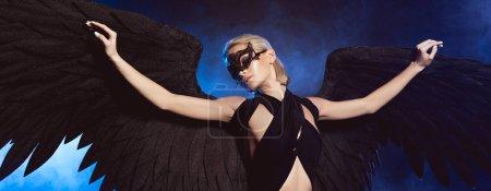 Photo pour Belle femme sexy avec masque de dentelle et des ailes d'ange noir posant sur fond bleu foncé - image libre de droit