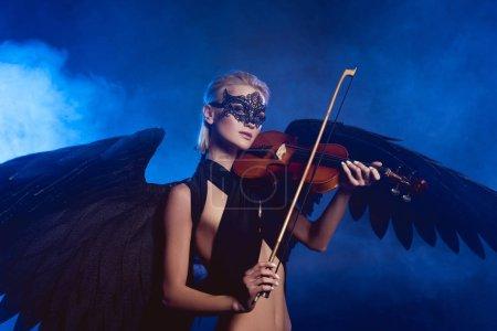 Foto de Hermosa mujer sexy con encaje máscara y alas de Ángel negro tocando el violín sobre fondo ahumado azul oscuro - Imagen libre de derechos