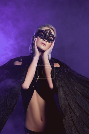 Photo for Beautiful sexy woman in lace mask and black angel wings touching face and posing on smoky violet background - Royalty Free Image