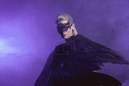Photo pour Belle femme en dentelle masque et ailes d'ange noir posant sur fond violet fumé avec espace de copie - image libre de droit