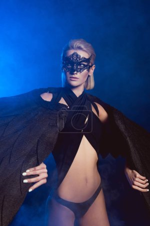 Photo for Beautiful sexy woman in lace mask and black angel wings posing and looking away on dark blue background - Royalty Free Image