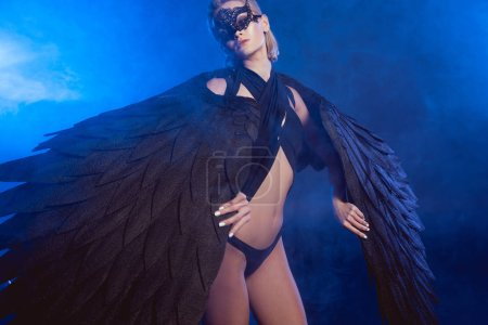 Photo for Beautiful sexy woman in lace mask holding black angel wings and posing on dark blue background - Royalty Free Image