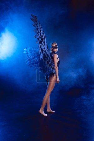 Photo pour Belle femme mystérieuse sexy en masque de dentelle et ailes d'ange noir posant sur fond fumé bleu foncé - image libre de droit