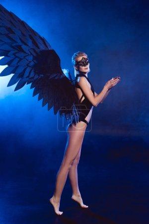 Foto de Hermosa mujer sexy con encaje máscara y alas de Ángel negro de pie de puntillas sobre fondo azul oscuro - Imagen libre de derechos