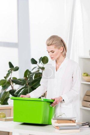 Photo pour Jolie femme regardant boîte lorsque vous êtes debout dans le bureau, environnement sauver la notion de recyclage - image libre de droit