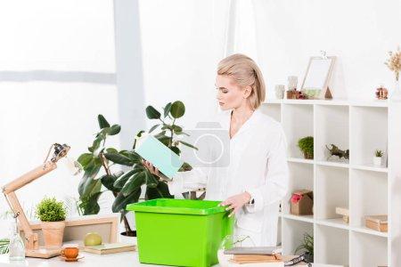 Photo pour Jolie femme holding paquet lait près de boîte en se tenant debout dans le bureau, environnement sauver la notion de recyclage - image libre de droit