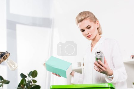 Photo for Attractive woman holding milk package and can in hands near recycling box while standing in office, environmental saving concept - Royalty Free Image