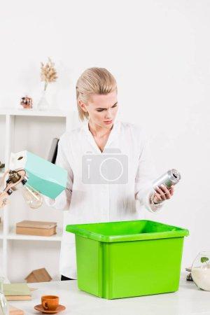 Photo pour Jolie femme regardant can tout en maintenant le paquet de lait près de boîte, environnement sauver la notion de recyclage - image libre de droit