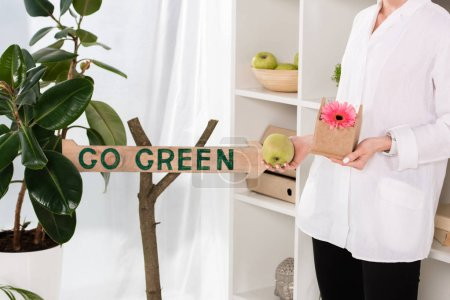 Photo for Cropped view of businesswoman holding small cardboard house with flower near go green sign in office, environmental saving concept - Royalty Free Image