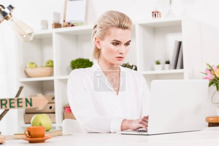 Photo for Attractive woman typing on laptop near cup with drink in office - Royalty Free Image