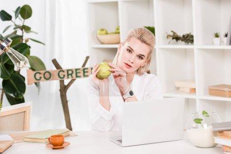 Foto de Mujer atractiva celebración de manzana verde y sentado junto a la señal ir verde, ambiental ahorro concepto - Imagen libre de derechos