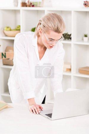Photo pour Jolie femme à lunettes en regardant ordinateur portable lorsque vous êtes debout dans le bureau - image libre de droit