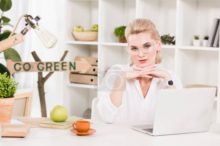 Photo for Attractive woman in glasses sitting near laptop with go green sign behind, environmental saving concept - Royalty Free Image