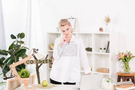 Photo for Attractive woman in glasses standing near laptop with go green sign behind, environmental saving concept - Royalty Free Image