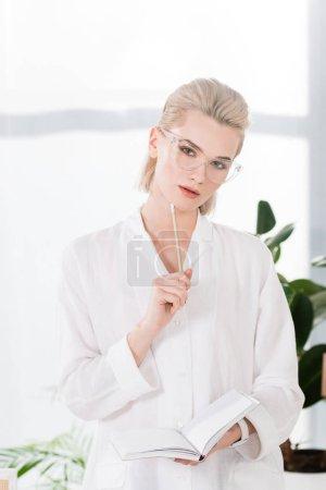 Nachdenkliche Geschäftsfrau in Brille mit Notizbuch und Bleistift im Büro