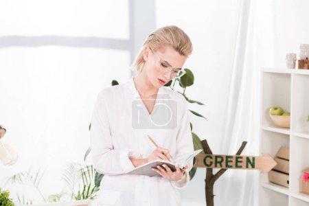Photo pour Femme d'affaires gentil dans des verres à écrire dans le cahier en se tenant debout dans le bureau, environnement économie concept - image libre de droit
