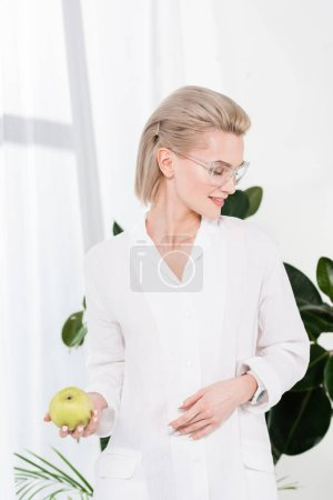 Photo for Cheerful businesswoman in glasses holding green apple in office - Royalty Free Image