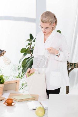 Foto de Hermosa mujer en gafas con eco bolsa cerca de escritorio en oficina, ambiental ahorro concepto - Imagen libre de derechos