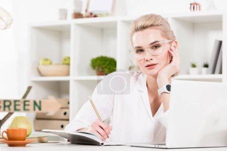 Photo pour Femme à lunettes écrire dans cahier près ordinateur portable au bureau, environnement économie concept - image libre de droit
