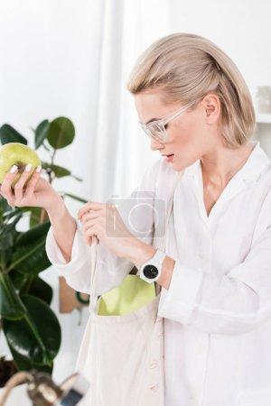 Photo pour Belle femme d'affaires dans les verres, tenant la pomme verte et de la recherche à l'intérieur du sac éco, environnement économie concept - image libre de droit