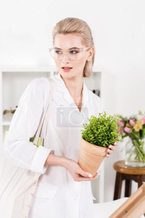Photo for Beautiful businesswoman in glasses holding green plant in office, environmental saving concept - Royalty Free Image