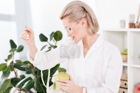 Photo pour Femme d'affaires gai dans les verres, tenant la pomme verte et de la recherche à l'intérieur du sac éco, environnement économie concept - image libre de droit