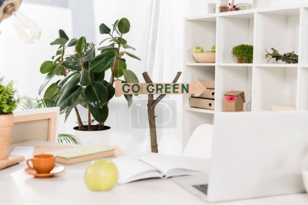 Photo for Workspace with apple and laptop near go green sign in modern office, environmental saving concept - Royalty Free Image